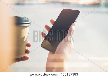 Close up of tablet and papper cup handing in girl hands