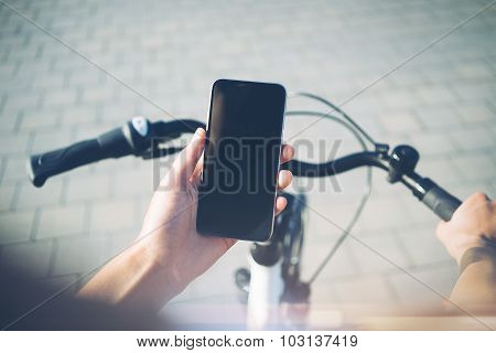 Girl using smartphone and bicycle for traveling in the city