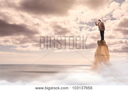 businessman with spyglass standing on the top of a mountain