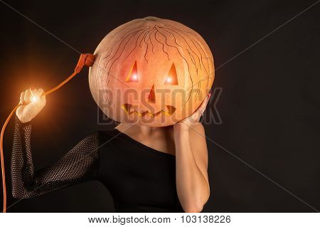woman recharges pumpkin head, concept of Halloween