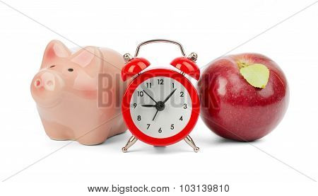 Fresh red apple with alarm clock and piggy bank