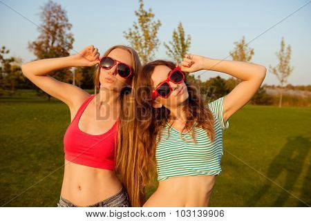 Two Sexy Young Slender Girls Holding Funny Glasses