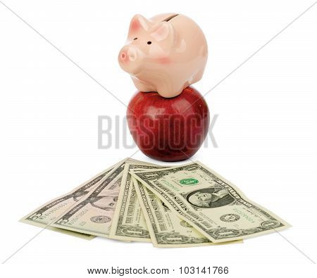 Fresh apple with money and piggy bank
