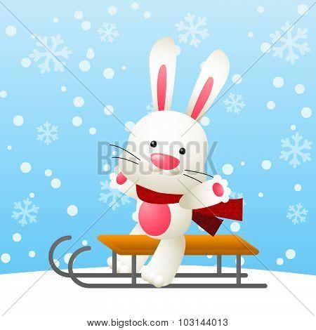 Cute white rabbit on a sled
