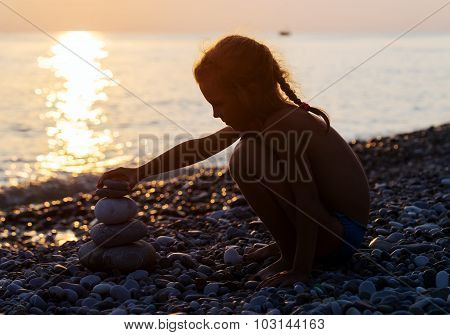 Silhouette Of Young Girl Puts Pyramid From Stones