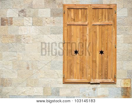 closed wooden window on a rocky wall