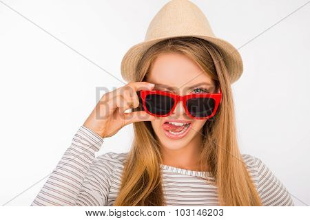 Happy Girl With A Hat Putting Glasses On Her Nose Showing Tongue
