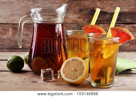 Iced tea with lemon and grapefruit on wooden background