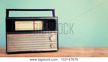 Retro radio on wooden table on turquoise background