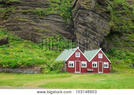 Red wooden cottage at campsite in Iceland