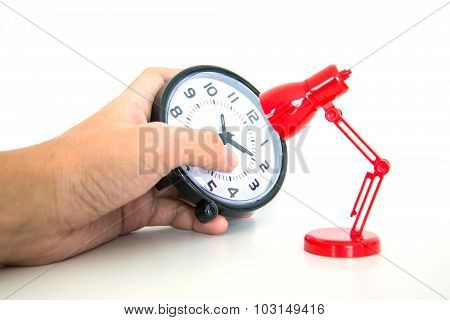 Hand Holding Alarm Clock With Red Desk Lamp
