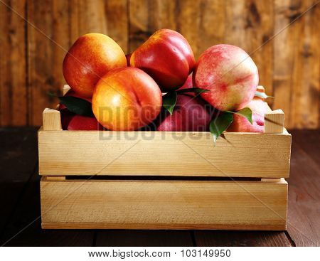 Fresh peaches in crate on wooden background