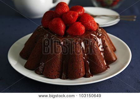 Delicious chocolate cake with strawberries in plate on table, closeup