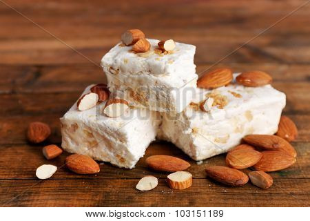 Sweet nougat with almonds on wooden background