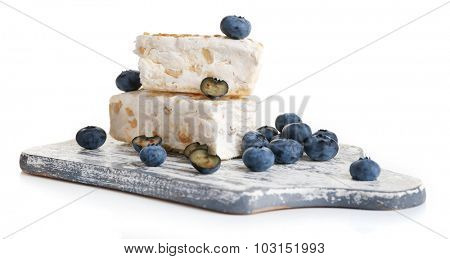 Sweet nougat with hazelnuts and blueberries isolated on white