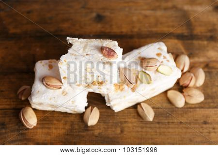 Sweet nougat with pistachios on wooden background