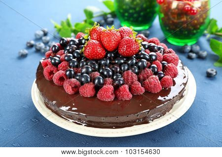 Delicious chocolate cake with summer berries on blue tablecloth background
