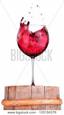 Glass of red wine on a wooden barrel