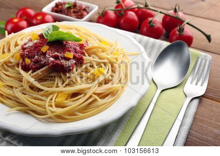 Spaghetti with tomato sauce, paprika and cheese on white plate, on color wooden background
