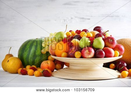 Heap of fresh fruits and berries on wooden background