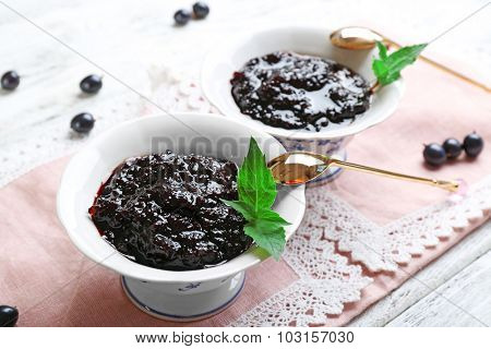 Tasty currant jam with berries on table close up