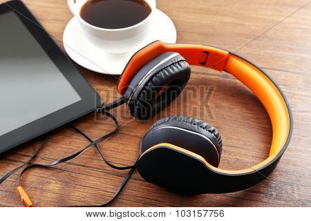 Headphones with tablet and cup of coffee on wooden table close up