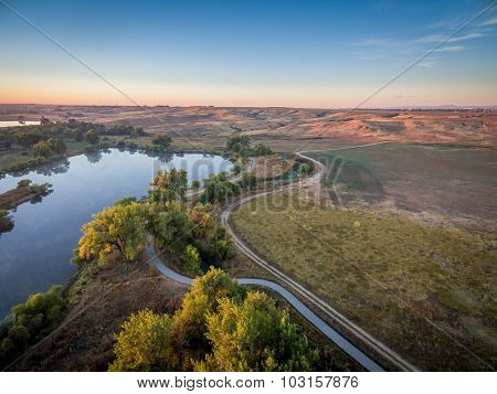aerial view of sunrise over Poudre River Trail with a bike path, ranch road and ponds