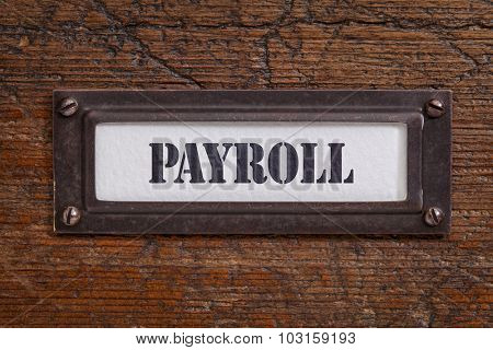 payroll - file cabinet label, bronze holder against grunge and scratched wood, financial concept
