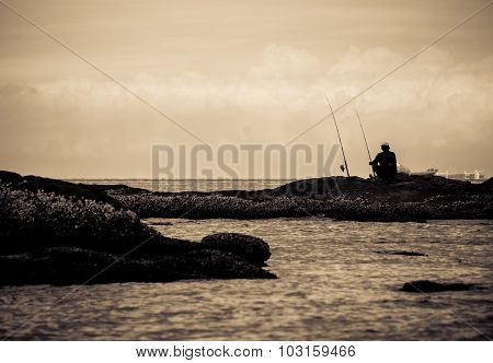 Silhouette Of People Fishing By The Sea