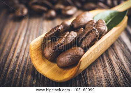 Coffee beans with leaf in spoon on wooden table close up