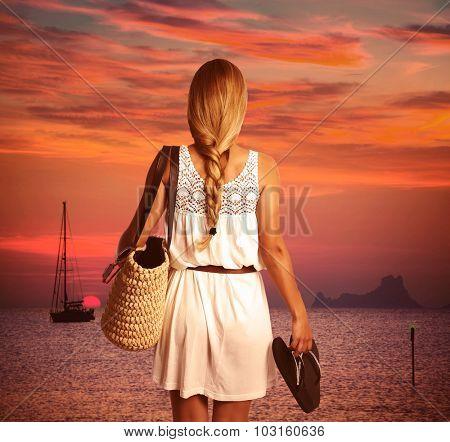 Blond braid tourist girl looking sunset holding flip flop in beach of Formentera photomount