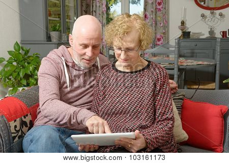 A Mother And Her Adult Son Looking At A Digital Tablet On A Sofa