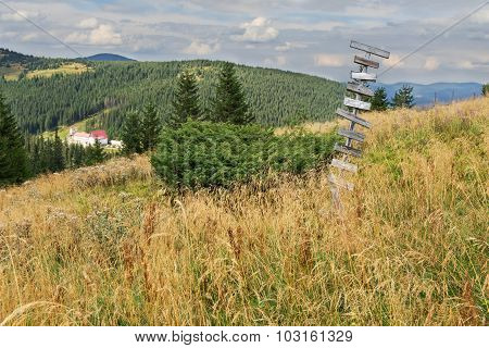 Old Wooden Signpost In The Mountains