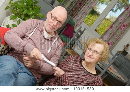 A Mother And Her Adult Son Looking Paper On A Sofa