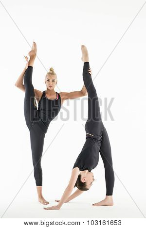 Two artistic gymnast doing paired exercises
