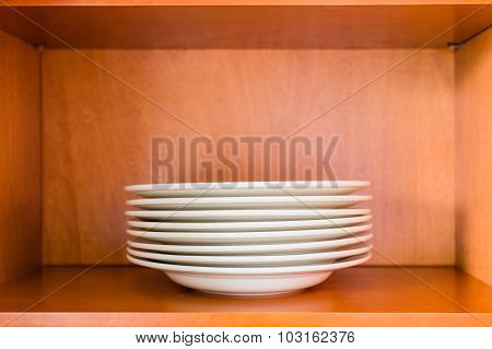 Organized minimalistic kitchen cabinet with a stack of white porcelain plates