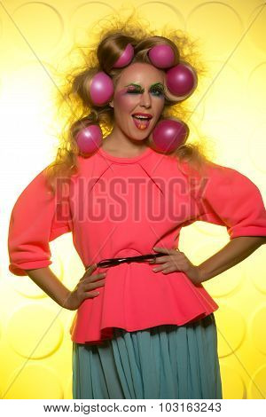 Girl with bright makeup and hair balls on a yellow background