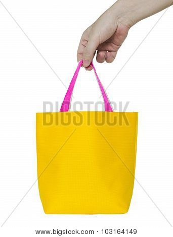 Hand Holding Yellow Fabric Bag Isolated On White