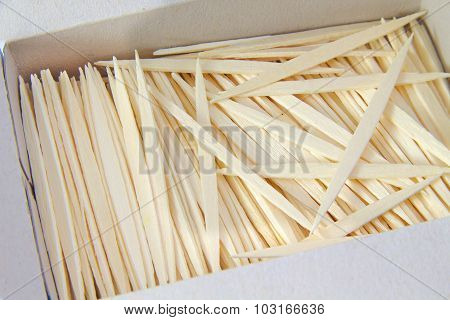 Bunch of plain brown toothpicks on white background