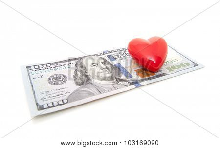 Red heart in hundred dollar note. All on white background.