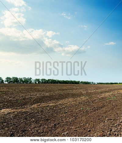 arable soil after harvesting and clouds in blue sky