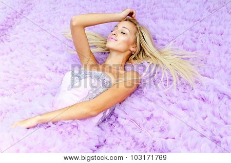 Young woman in a pink dress lying