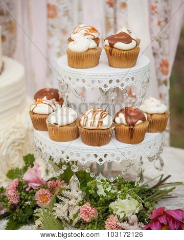 cream and caramel cupcakes on a white stand with flowers and a cloth backdrop