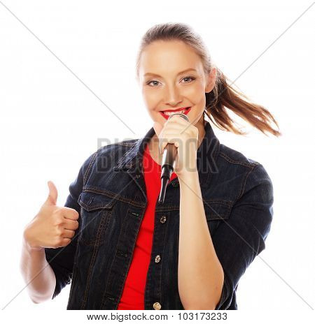 Happy singing girl. Beauty woman wearing red t-shirt  with microphone over white background.