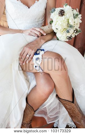 bride showing her cowboy boots and garter and bouquet