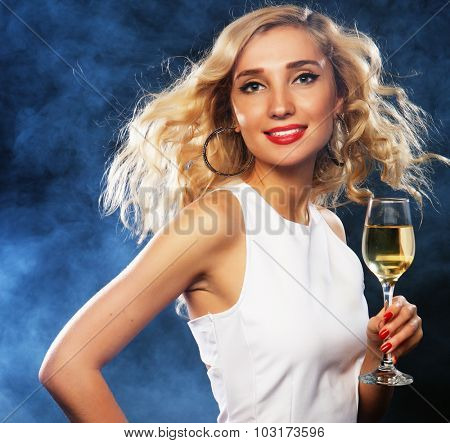 smiling woman in evening dress with glass of sparkling wine