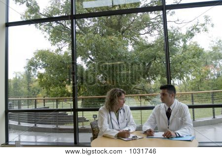 2 Doctors Talking At Table