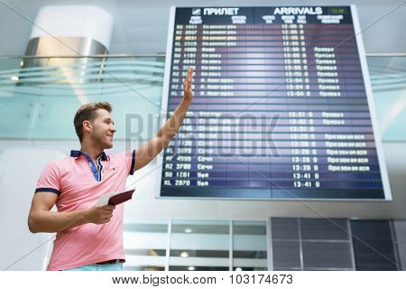 Young man with a passport at the board