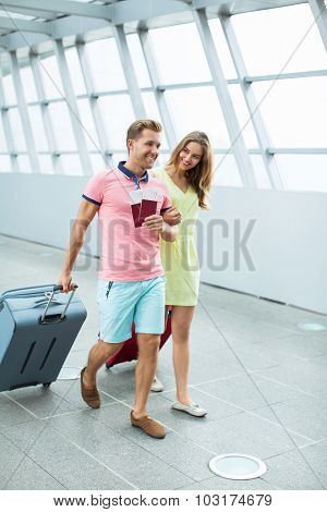 Smiling couple with a suitcase  at the airport