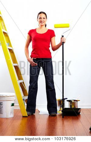 Beautiful woman with painting roller. House renovation.